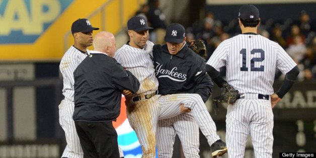 NEW YORK, NY - OCTOBER 13:  Derek Jeter #2 of the New York Yankees is carried off the field by trainer Steve Donohue (L) and