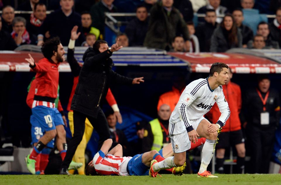 Atletico Madrid's midfielder Gabi (down) reacts after being injured next to Real Madrid's Portuguese forward Cristiano Ronald