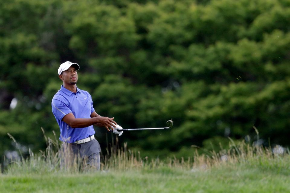Tiger Woods watches his shot on the first hole during the first round of the U.S. Open golf tournament at Merion Golf Club, T