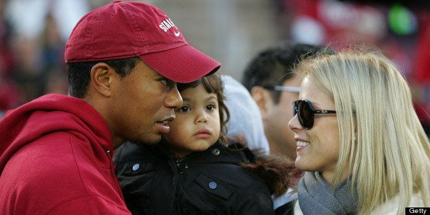 PALO ALTO, CA - NOVEMBER 21:  Honorary Standford Cardinal captain Tiger Woods holds his daugher, Sam, and speaks to his wife,