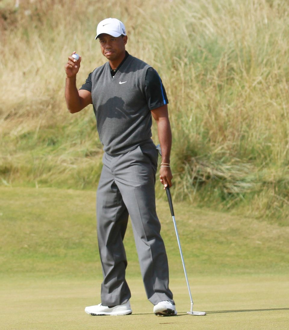 Tiger Woods of the United States holds up his ball after putting on the second green during the third round of the British Op
