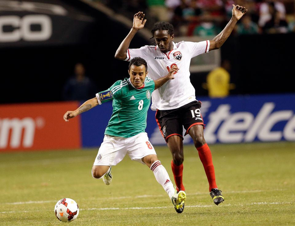 Mexico's Luis Montes (8) moves the ball as Trinidad & Tobago's Keon Daniel (19) defends during the second half in the quarter