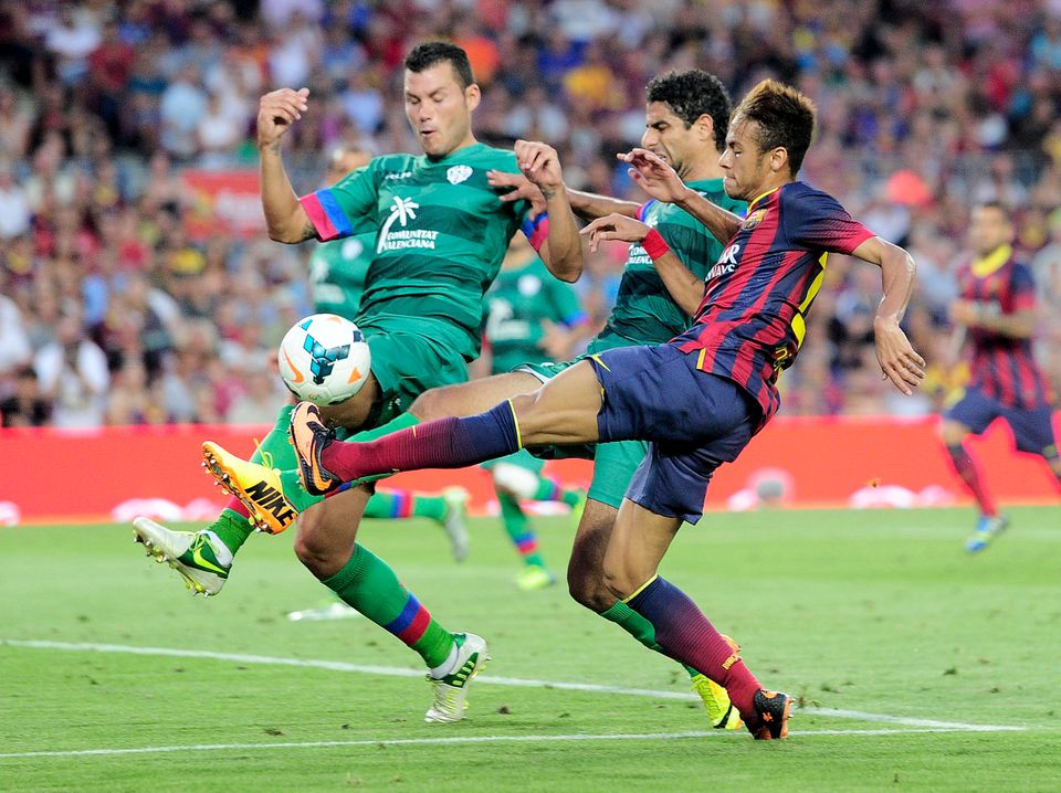 Barcelona's Brazilian forward Neymar da Silva Santos Junior (R) vies with Levante's defender David Navarro (L) and Levante's