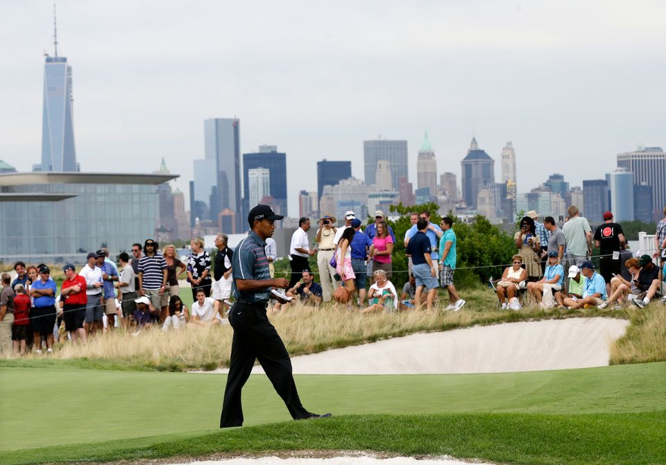 With the Manhattan skyline visible in the distance, Tiger Woods walks on the second hole during the second round of The Barcl