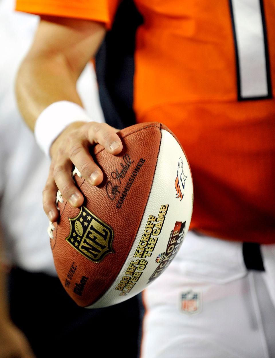 Denver Broncos quarterback Peyton Manning holds the game ball after an NFL football game against the Baltimore Ravens, Thursd