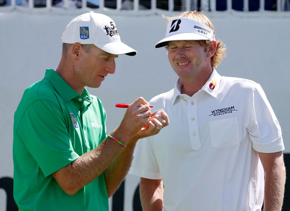 Brandt Snedeker, right, smiles as Jim Furyk marks his ball during the third round of the BMW Championship golf tournament at