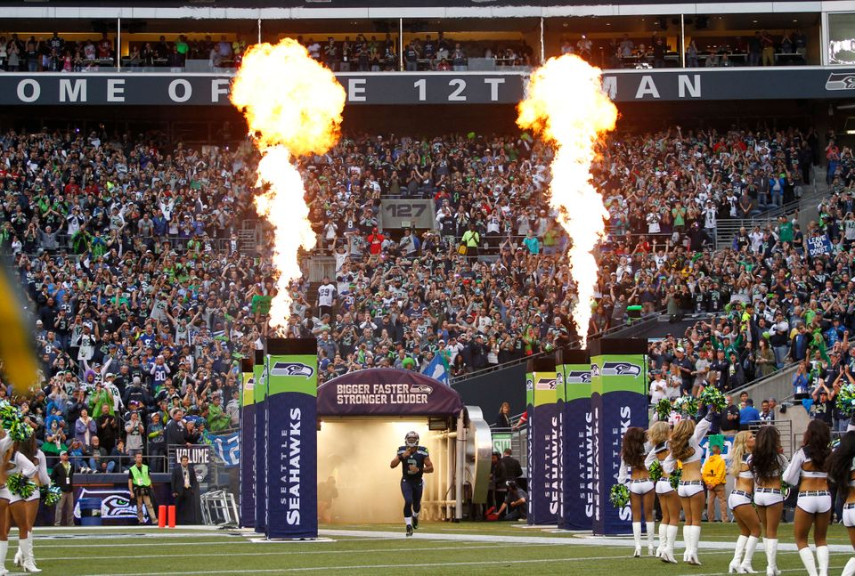 Seattle Seahawks quarterback Russell Wilson runs out of the tunnel as fire effects go off to take the field for the Seahawks'