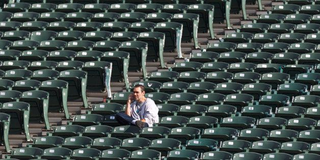 OAKLAND, CA - OCTOBER 21:  A fan sits among empty seats while talking on a cell phone before the game between the Oakland Rai