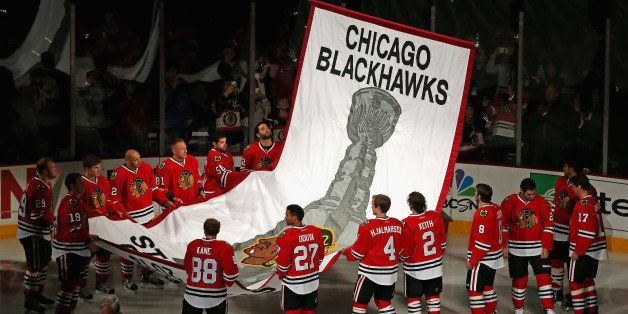 CHICAGO, IL - OCTOBER 01:  Members of the Chicago Blackhawks watch as the 2013 Stanley Cup Championship banner is hung during