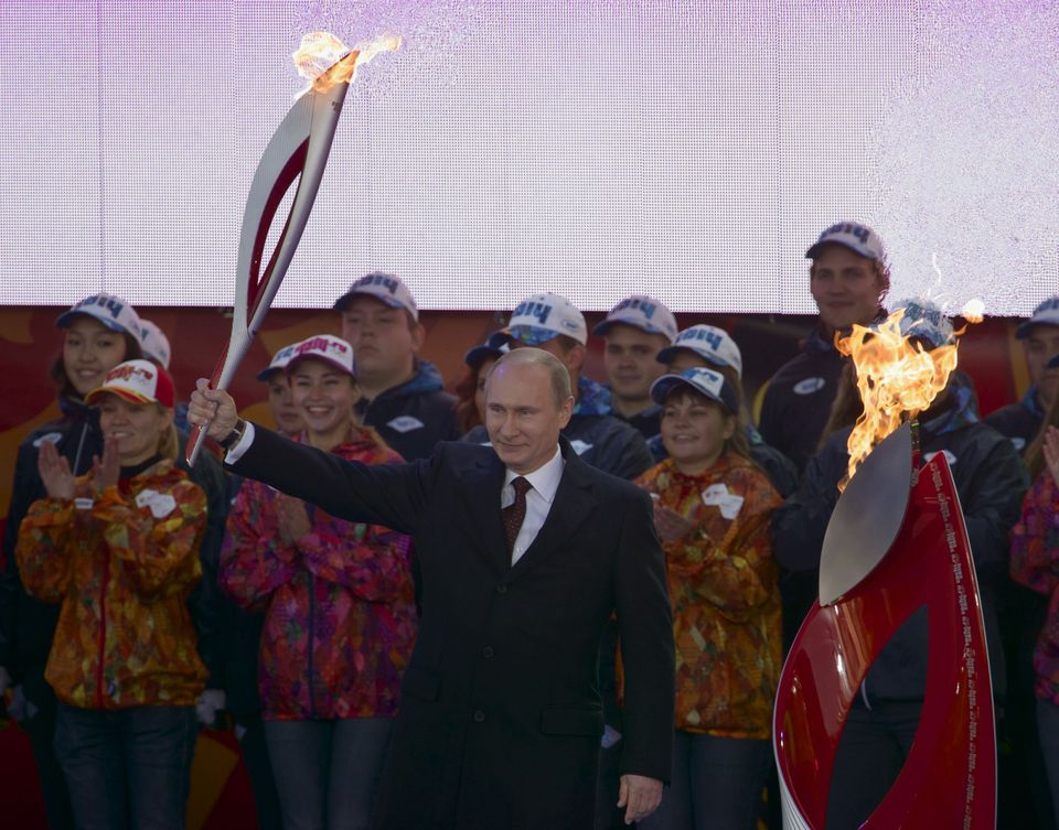 Russian President Vladimir Putin, centre, smiles as he lights the Olympic flame with a torch, at the Red Square, Moscow, Sund