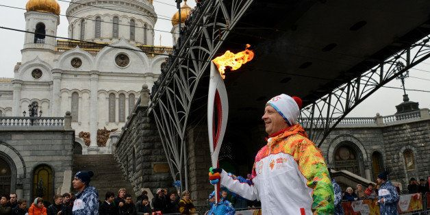 One of the participants of the Sochi 2014 Winter Olympic torch relay runs near the Christ the Saviour Cathedral in Moscow, on