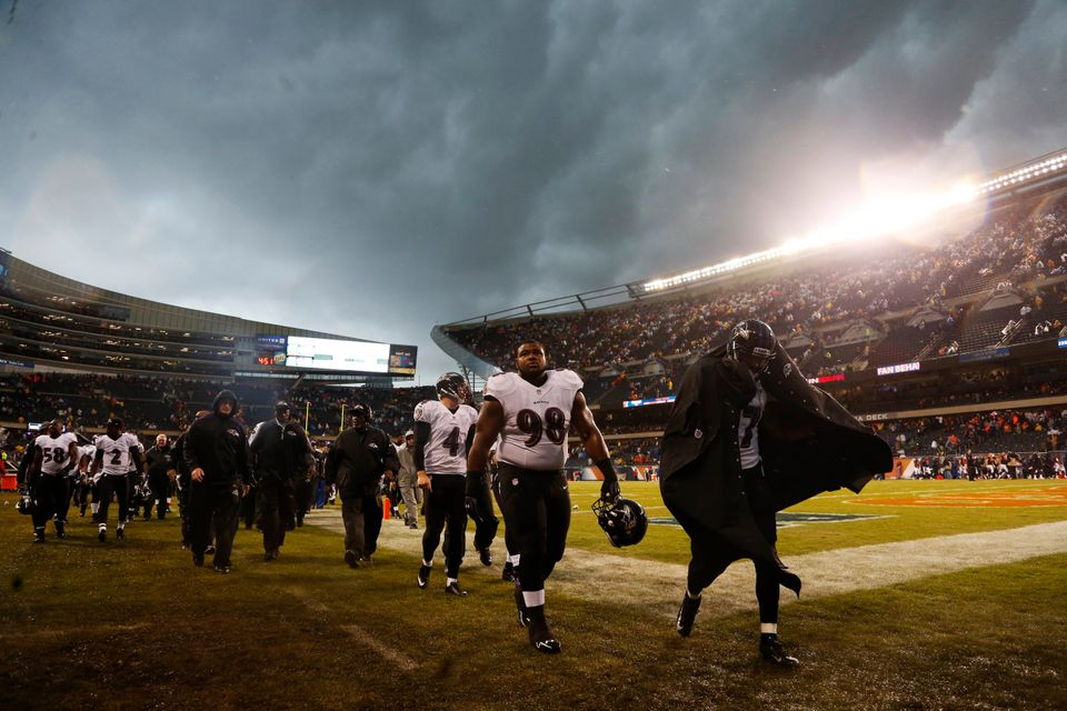 Baltimore Ravens players leave the field as play was suspended for a severe thunderstorm blowing through Soldier Field during