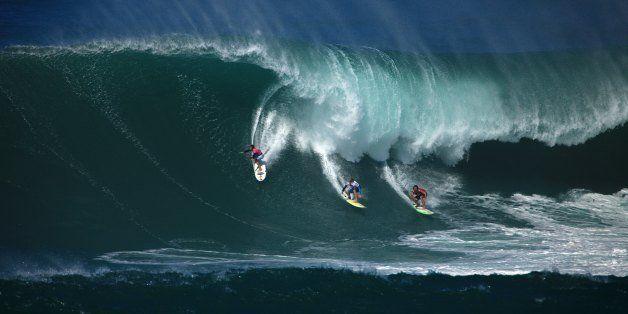 NORTH SHORE, HAWAII - DECEMBER 8:  Surfers ride a wave at the Eddie Aikau Big Wave Invitational at Waimea Bay, North Shore, H