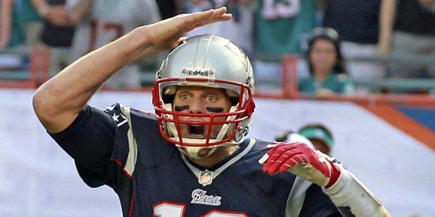 New England Patriots quarterback Tom Brady gives signals during an NFL game against the Miami Dolphins at Sun Life Stadium in