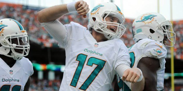 Miami Dolphins' Ryan Tannehill celebrates a touchdown to Mike Wallace in the second quarter against the New England Patriots