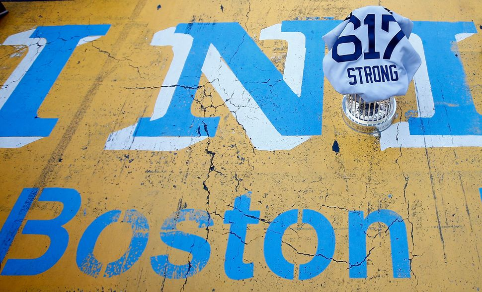 """The Red Sox's World Series trophy and a """"Boston Strong 617"""" jersey sit on the finish line of the Boston Marathon during the W"""