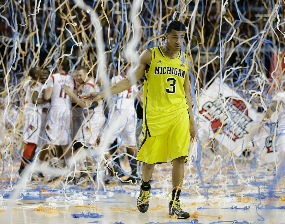 Michigan guard Trey Burke walks off the court as Louisville celebrate their win during the  NCAA Final Four championship game