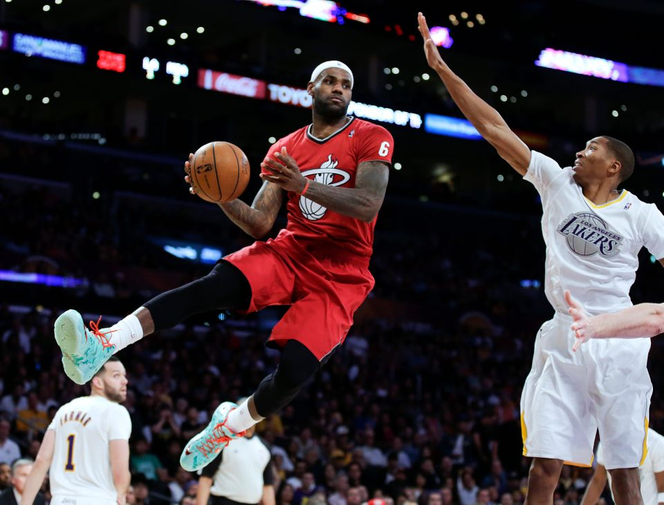 Miami Heat forward LeBron James, left, passes around Los Angeles Lakers guard Wesley Johnson during the second half of an NBA