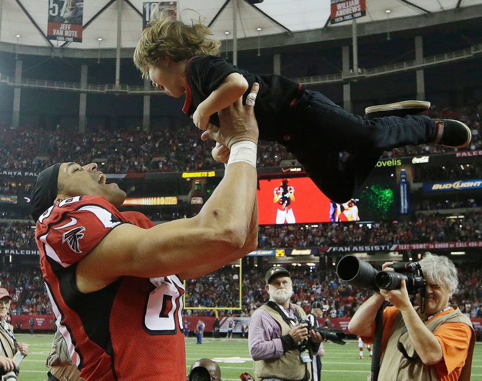 Atlanta Falcons tight end Tony Gonzalez (88) holds his son river Gonzales, 3, during a celebration of Gonzalez career before