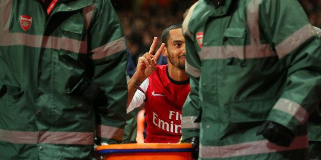LONDON, ENGLAND - JANUARY 04:  The injured Theo Walcott of Arsenal makes a 2-0 gesture to the Tottenham fans as he is stretch