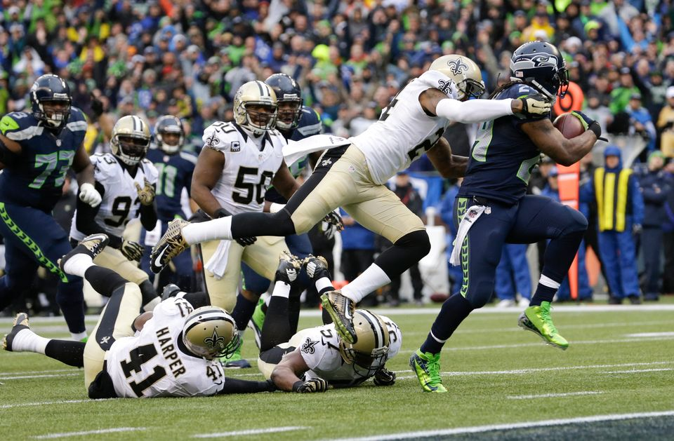 Seattle Seahawks running back Marshawn Lynch, right, runs past New Orleans Saints cornerback Corey White (24) for a 15-yard t