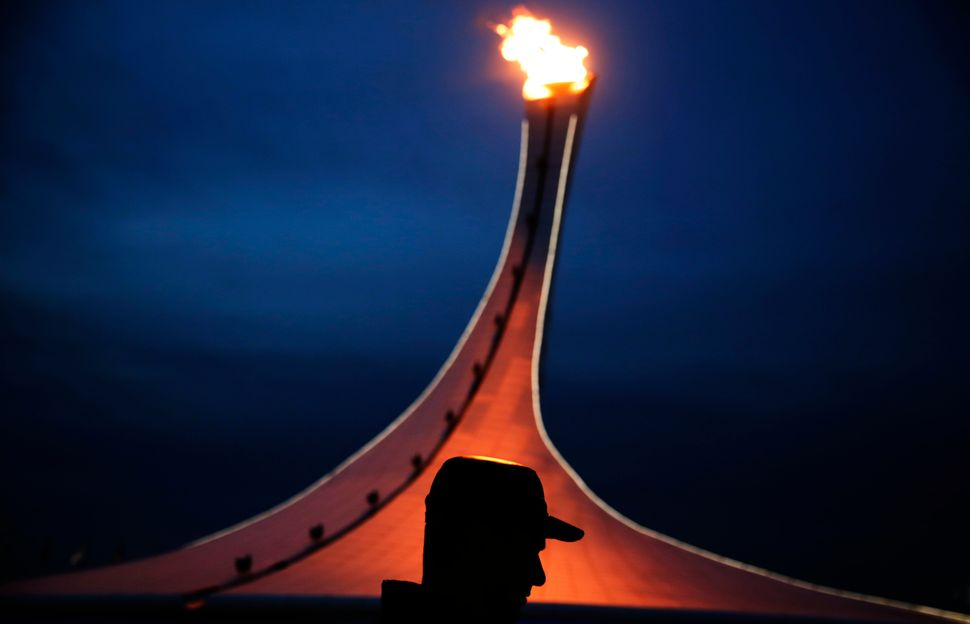A visitor to the Olympic Park is silhouetted while walking past the Olympic cauldron at the 2014 Winter Olympics, Feb. 20, 20
