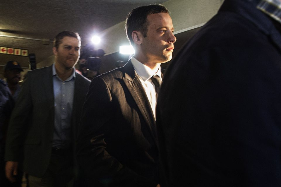 South African Paralympian athlete Oscar Pistorius (C)arrives  at the High Court in Pretoria on September 11, 2014, to face ju
