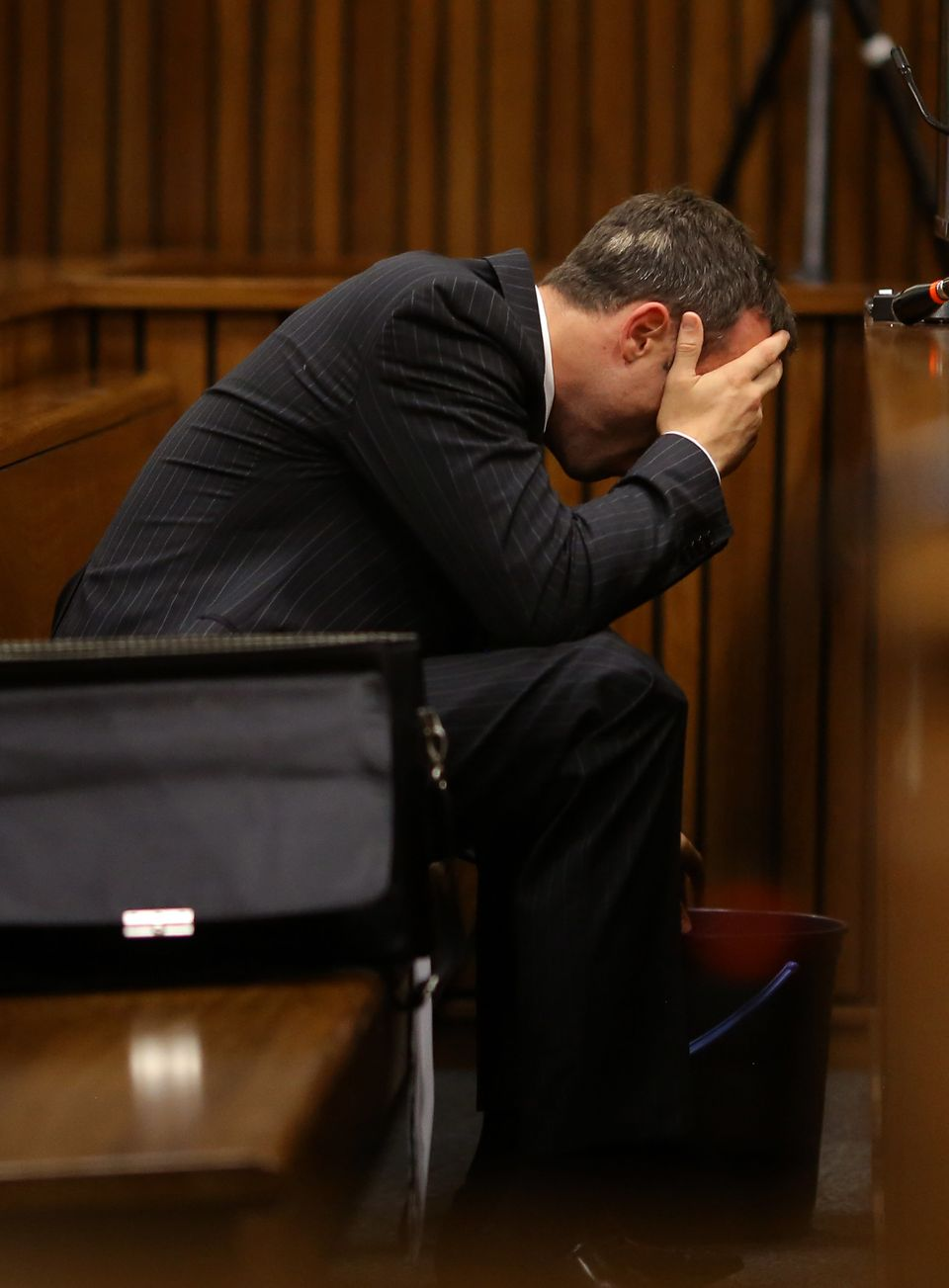 Olympic and Paralympic track star Oscar Pistorius vomits during a hearing on the sixth day of his trial for the 2013 murder o