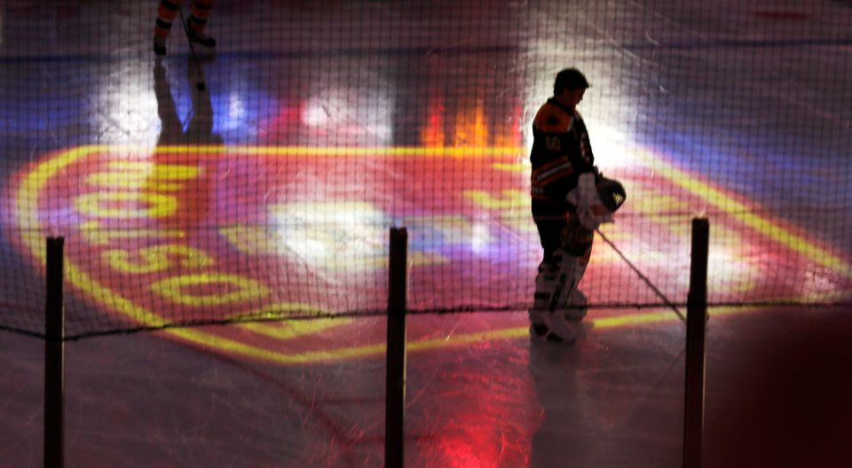 Boston Bruins goalie Tuukka Rask pauses as the Boston Fire Department emblem is projected onto the ice, honoring two Boston f