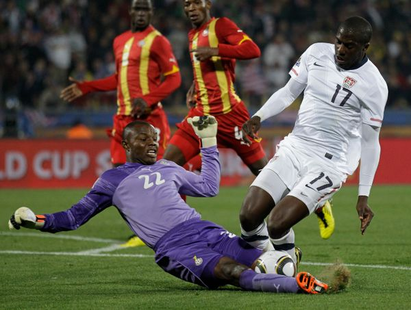 Ghana goalkeeper Richard Kingson, bottom, blocks United States' Jozy Altidore, right, during the World Cup round of 16 soccer