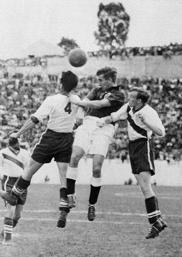 English midfielder Thomas Finney (C) tries to head the ball between American defenders Charlie Colombo and Walter Bahr 29 Jun