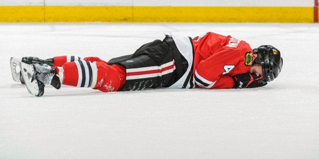 CHICAGO, IL - MAY 4: Niklas Hjalmarsson #4 of the Chicago Blackhawks lays on the ice after blocking a shot and getting hit wi