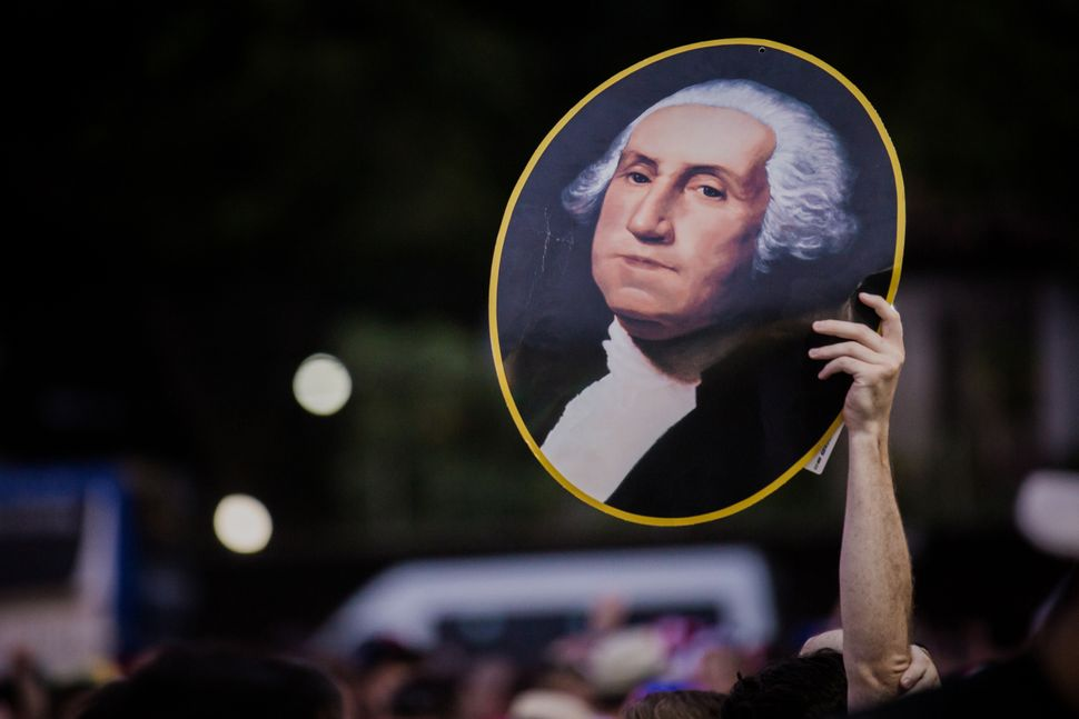 A fan holds up a picture of George Washington before the Group G match between Ghana and USA at Estadio das Dunas during the