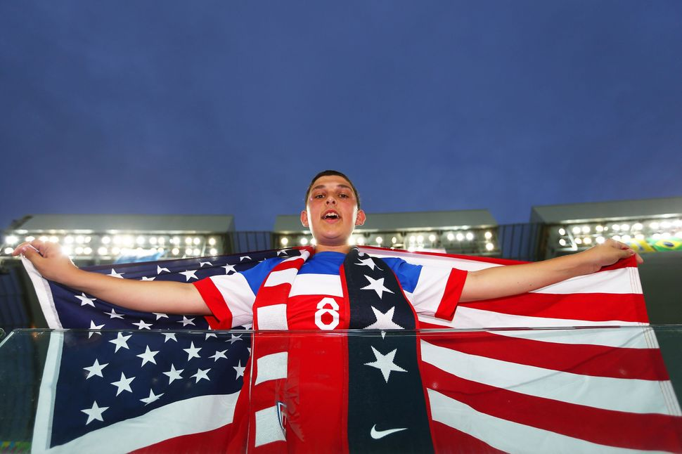 A fan of the United States holds an American flag prior to the 2014 FIFA World Cup Brazil Group G match between Ghana and the