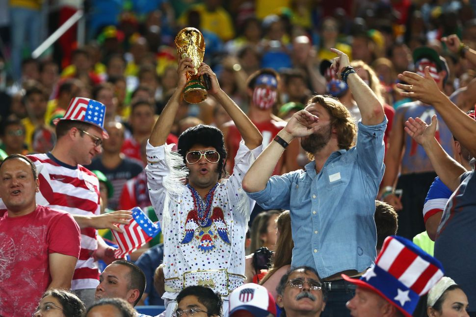 A United States fan dressed as Elvis holds up a replica of the World Cup trophy during the 2014 FIFA World Cup Brazil Group G
