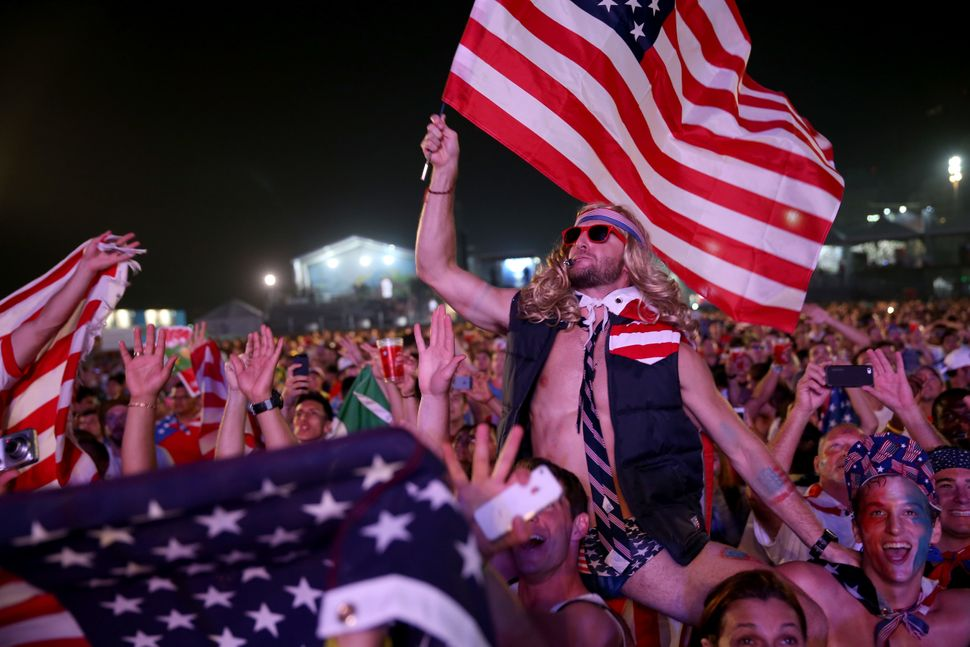 American soccer fans wait for their team to play against Ghana at the FIFA World Cup Fan Fest on Copacabana beach on June 16,