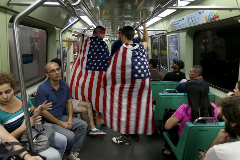 American soccer fans, Edward Amador (L) and Phillip Amador from Las Cruces ride the subway as they wait for the USA to play i