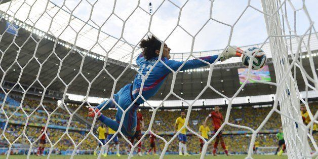 Mexico's goalkeeper Guillermo Ochoa dives for the ball during a Group A football match between Brazil and Mexico in the Caste