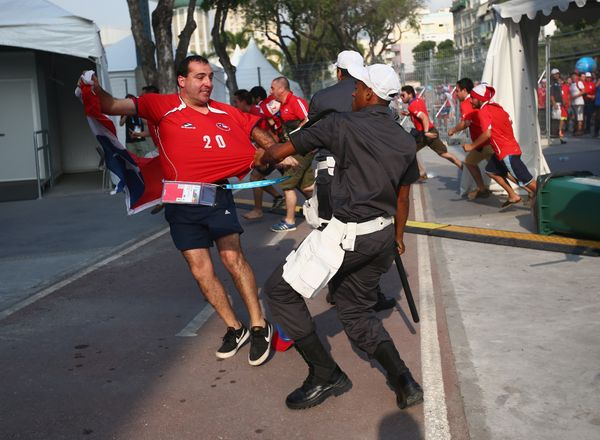 RIO DE JANEIRO, BRAZIL - JUNE 18:  Security personnel attempt to control Chilean fans breaking through a gate outside the sta