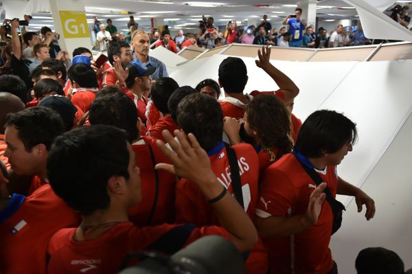 Chile's fans, who managed to enter the stadium without tickets, knock over a parition in the press area, before the Group B f
