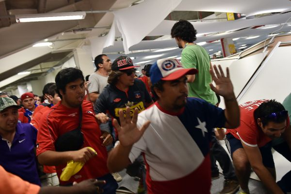 Chile's fans, who managed to enter the stadium without tickets, knock over a partition in the press area, before the Group B