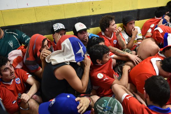 Chile's fans, who managed to enter the stadium without tickets, organize a sit-in in the press area before the Group B footba