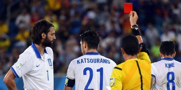 Greece's midfielder Kostas Katsouranis (C) is given the red card after a foul on Japan's midfielder Makoto Hasebe during a Gr