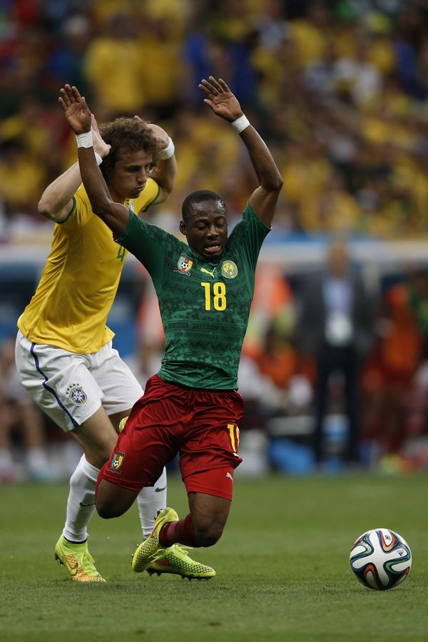 Brazil's defender David Luiz (L) and Cameroon's midfielder Enoh Eyong vie for the ball during the Group A football match betw