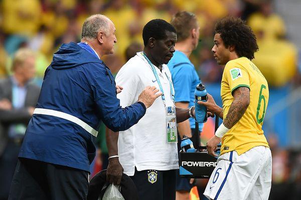 Brazil's defender Marcelo (R) drinks water as he listens to Brazil's coach Luiz Felipe Scolari (L) during the Group A footbal