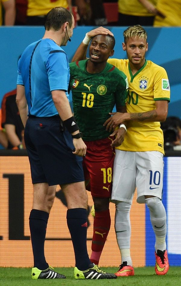 Brazil's forward Neymar (R) patsone Cameroon's midfielder Enoh Eyong on the head during a Group A football match between Came