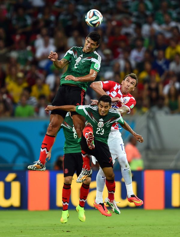 RECIFE, BRAZIL - JUNE 23:  Francisco Javier Rodriguez of Mexico goes up for a header against Mario Mandzukic of Croatia durin