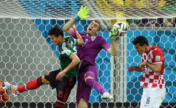 Croatia's goalkeeper Stipe Pletikosa (C) and Croatia's defender Dejan Lovren (R) vie for the ball with Mexico's defender Hect