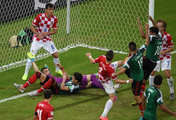Mexico's defender Hector Moreno (L, on ground) and Croatia's goalkeeper Stipe Pletikosa (wearing purple) clash during a Group