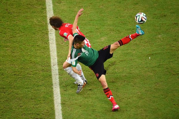 RECIFE, BRAZIL - JUNE 23:  Oribe Peralta of Mexico and Ivan Rakitic of Croatia compete for the ball during the 2014 FIFA Worl